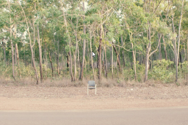 an office chair in front of a wood on a dusty road
