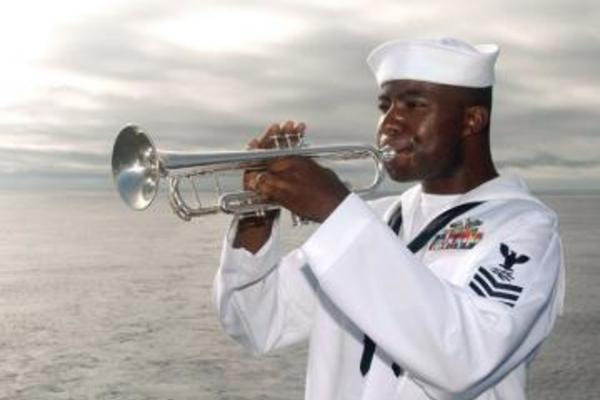 A man in a sailor's uniform playing the bugle