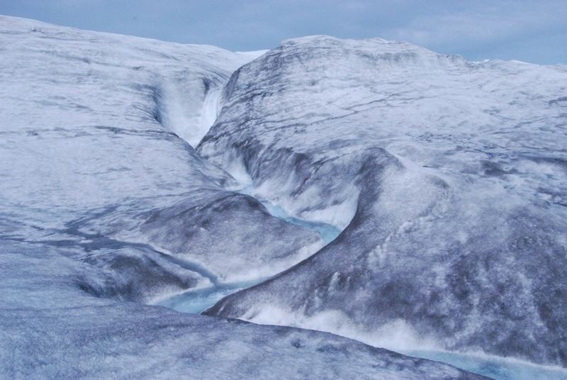 Blue meltwater cuts a jagged path through an icy landscape